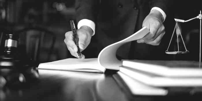 Schreibtisch mit Mandantenakten und Waage - sinnbild für Gerechtigkeit
