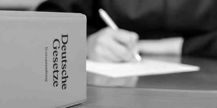 """Gesetzbuch """"Deutsche Gesetze"""" auf einem Schreibtisch mit Notizzettel und Händen vom Rechtsanwalt"""