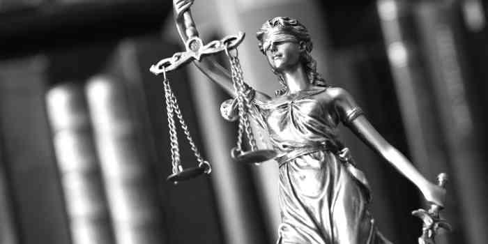 Kleine Statue der Justitia vor Gesetzbüchern