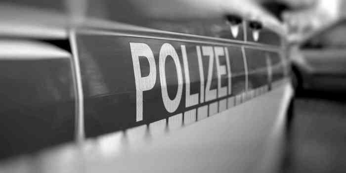 """Großaufnahme Aufschrift """"Polizei"""" auf Einsatzfahrzeug bei einer Durchsuchung"""